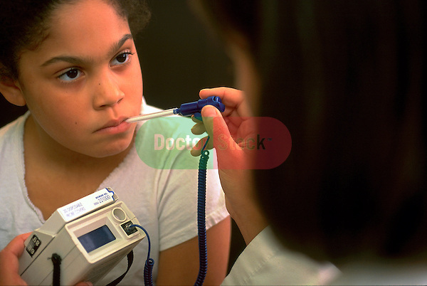doctor taking temperature of young girl