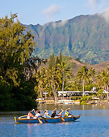 Women's crew paddle up a Kailua canal during morning practice