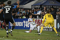 Shea Salinas (center) kicks the ball between Ramiro Corrales (12) and Jon Busch (18). The San Jose Earthquakes tied the Vancouver Whitecaps 2-2 at Buck Shaw Stadium in Santa Clara, California on July 20th, 2011.