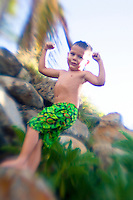 Boy in swimsuit flexes his arms. Palm tree in background. Blurred edges for artistic effect.