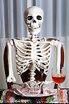 Skeleton waits for dinner at table with full place setting and wine.