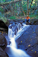 A young boy, age 8,sitting beside a waterfall on Kapena stream