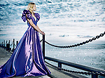 Young blond woman wearing a beautiful long blue dress, evening gown, standing at waterfront looking at the sea Image © MaximImages, License at https://www.maximimages.com