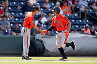 Catcher Christopher Burgess (24) of the Aberdeen IronBirds is greeted by manager Kyle Moore (44) after hitting a home run in a game against the Greenville Drive on Sunday, July 11, 2021, at Fluor Field at the West End in Greenville, South Carolina. (Tom Priddy/Four Seam Images)