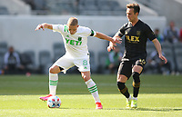 LOS ANGELES, CA - APRIL 17: Alex Ring #8  of Austin FC battles for a ball during a game between Austin FC and Los Angeles FC at Banc of California Stadium on April 17, 2021 in Los Angeles, California.