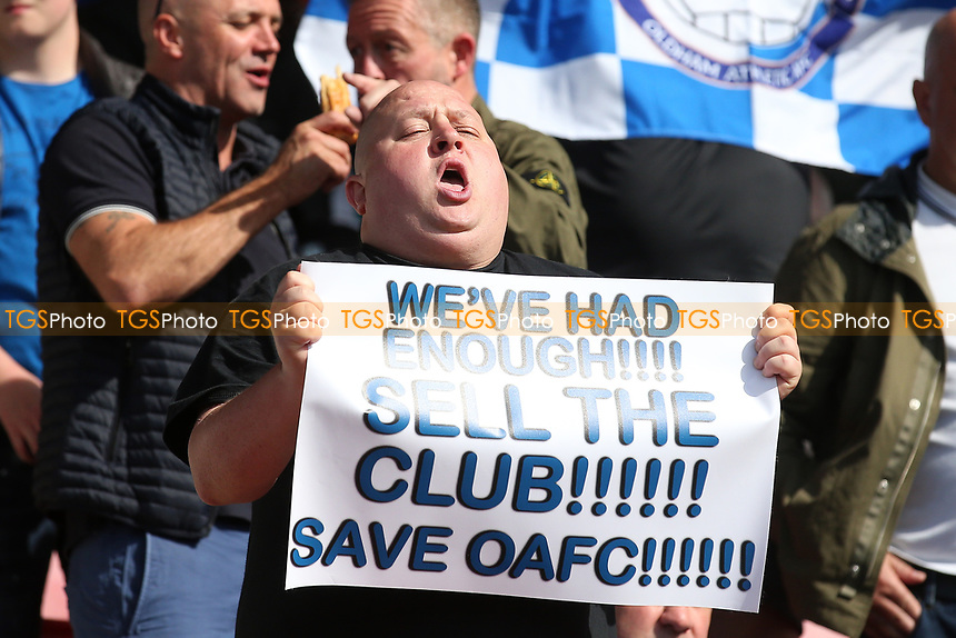 An Oldham fan with a 'Sell The Club' banner protests during Leyton Orient vs Oldham Athletic, Sky Bet EFL League 2 Football at The Breyer Group Stadium on 11th September 2021