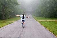 Two bicycle riders travel on foggy road in Gettysburg, PA.