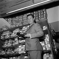 """Magasin """"Justo Sport"""", 26 rue Saint-Antoine-du-T. 23 mai 1966. Just Fontaine (footballeur) dans son magasin. Plan taille du joueur tenant une chaussure à crampon dans ses mains (contre-plongée) ; en arrière-plan étagères avec boîtes à chaussures."""