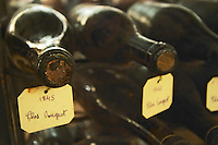 In the underground wine cellar: lying bottles in the treasure chamber where the oldest bottles are kept Two old bottles of Clos de Vougeot 1845 the oldest bottles in the cellar and one bottle from 1846. Red Burgundy wine vaulted vault ceiling with contrasting lights, Maison Louis Jadot, Beaune Côte Cote d Or Bourgogne Burgundy Burgundian France French Europe European