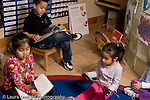 Preschool Headstart 3-5 year olds two girls and a boy sitting separately looking at picture books parallel play horizontal