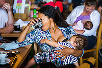 A mother drinking a cup of tea or coffee while breastfeeding in a cafe. Big Latch On event,Dorset, England, UK<br /> <br /> 02/08/2014<br /> <br /> <br /> © Paul Carter / wdiip.co.uk