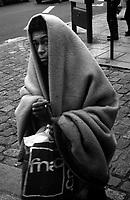 Paris (île de france)<br /> <br /> Femme sans abris marchant avec une couverture sur elle.<br /> <br /> Homeless woman walking with a blanket over her.
