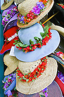 Shoppers enjoy a selection of colorful straw hats adorned with vivid flower leis that add that extra fashion flare.