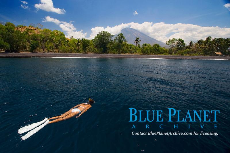 Snorkeler and black sand beach near Mt. Agung volcano, East Coast Bali, Indonesia,