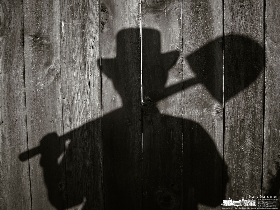 Man holding shiovel is cast on weathered wooden fence in his backyard.