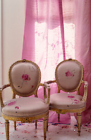 A pair of Louis XVI giltwood armchairs upholstered in hand-painted silk stands against a pale pink curtain