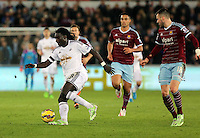 Pictured: Bafetimbi Gomis of Swansea (L) against Carl Jenkinson of West Ham (R) Saturday 10 January 2015<br /> Re: Barclays Premier League, Swansea City FC v West Ham United at the Liberty Stadium, south Wales, UK