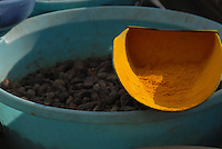 A metal scoop yellowed with turmeric powder contrasts to a blue plastic tub of black cardamom seeds at the Shimla bazaar, India.