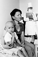 Kazakhstan. Semipalatinsk. Regional Children Clinical Hospital. Arnzhan Kunysbayeva (L) is a bald girl who suffers from cancer disease. She was born in 2004 in the village of Preobrazhenka, near the Semipalatinsk Polygon ( called today National Nuclear Center of Kazakhstan). Arnzhan Kunysbayeva seats on a bed, her mother holds her daughter in her arms. The child is a third (or four)generation victim of the 456 atomic testing - 116 atmospheric, 340 underground - from 1949 to 1989. The regions high frequency of cancer diseases is primarily due to fallout from nearby nuclear test sites. Arnzhan Kunysbayeva shows the human and environmental effects of nuclear radiation, genetic contamination and pollution from atomic tests programs of the former Soviet Union. Semey is the Kazakh name for Semipalatinsk and is located in the Eastern Kazakhstan Province. © 2008 Didier Ruef