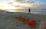 A Palestinian man walks past a 2018 sand writing at a beach in Gaza City on December 31, 2017 on the last day of the year. Photo by Ashraf Amra