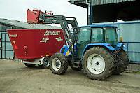 Front-end loader on a tractor with grab loading maize silage into a mixer wagon for feeding to dairy cattle.