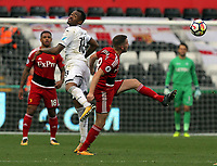 (L-R) Jordan Ayew of Swansea City battles for a header against Tom Cleverley of Watford during the Premier League match between Swansea City and Watford at The Liberty Stadium, Swansea, Wales, UK. Saturday 23 September 2017