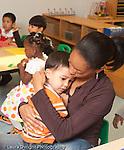 Education preschool 2-3 year olds separation sad boy sitting in teacher's lap