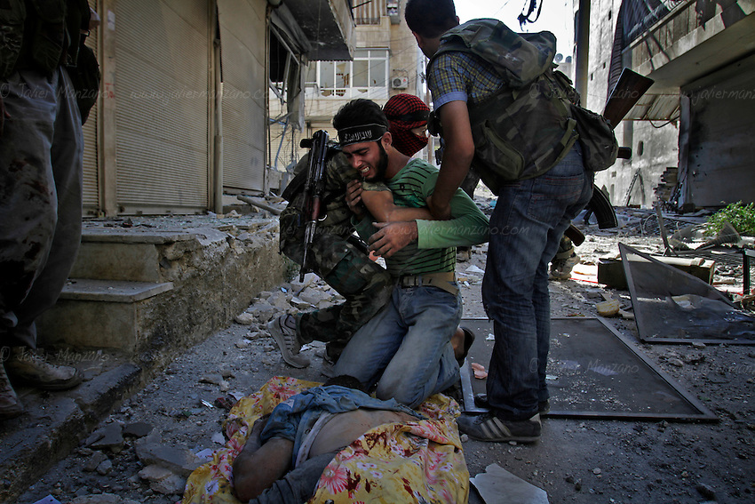 A Free Syria Army soldier reacts to the death of one of his comrades who died attempting to take out a Syria Army tank during intense clashes in the al-Qoob district of Aleppo. ..© Javier Manzano