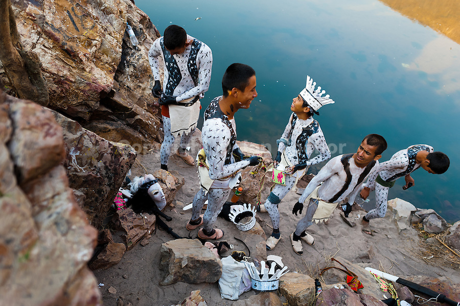 """Cora Indian boys, painting each other their bodies, prepare themselves for the sacred ritual ceremony of Semana Santa (Holy Week) in Jesús María, Nayarit, Mexico, 21 April 2011. The annual week-long Easter festivity (called """"La Judea""""), performed in the rugged mountain country of Sierra del Nayar, merges indigenous tradition (agricultural cycle and the regeneration of life worshipping) and animistic beliefs with the Christian dogma. Each year in the spring, the Cora villages are taken over by hundreds of wildly running men. Painted all over their semi-naked bodies, fighting ritual battles with wooden swords and dancing crazily, they perform demons (the evil) that metaphorically chase Jesus Christ, kill him, but finally fail due to his resurrection. La Judea, the Holy Week sacred spectacle, represents the most truthful expression of the Coras' culture, religiosity and identity."""