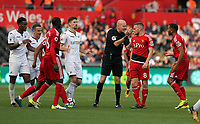 Referee Lee Mason (C) awards a foul kick to Swansea during the Premier League match between Swansea City and Watford at The Liberty Stadium, Swansea, Wales, UK. Saturday 23 September 2017