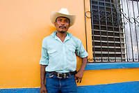 Close up of local man with cowboy hat with colorful wall in Copan Ruinas Honduras downtown city actio