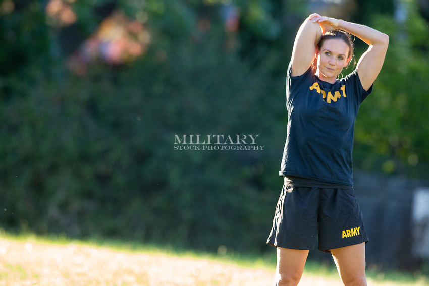 Solo portrait of a US Military woman photographed in Army T-shirt exercising in natural light. Stock photo for sale for advertising.