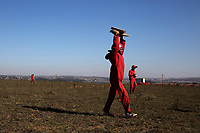 A member of the Red Ants carries off rocks used to mark out shacks on land by squatters intending set up an informal settlement. The Red Ants are a controversial private security company often hired to clear squatters from land and so-called 'hijacked' properties.