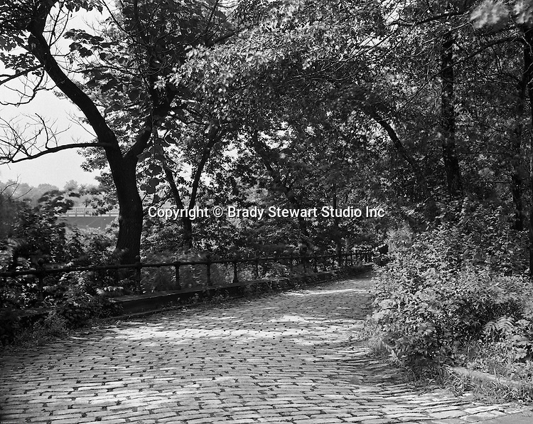 Pittsburgh PA:  View of a walking path in Frick Park. The park was created after a gift was made to the city of Pittsburgh by Henry Clay Frick.  When he died in 1919, Frick bequeathed to the city 151 acres south of his Point Breeze mansion, Clayton, and provided a $2 million trust fund to help create the park and assist with its long-term maintenance. The city began moving in earnest to create the park in 1925, when it acquired 190 additional acres, presumably with the goal to create a park of similar size and scope to Schenley and Highland Parks. The park officially opened in 1927.