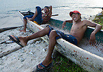 Two young Kuna guys hang out in a Cayuko, Dug-out canoe on Isla Pelikano, San Blas Islands, Kuna Yala, Panama