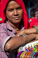 India, Dehradun.  Young Woman from Rajasthan Selling Bracelets in the Market.  Note her Nose Ring.