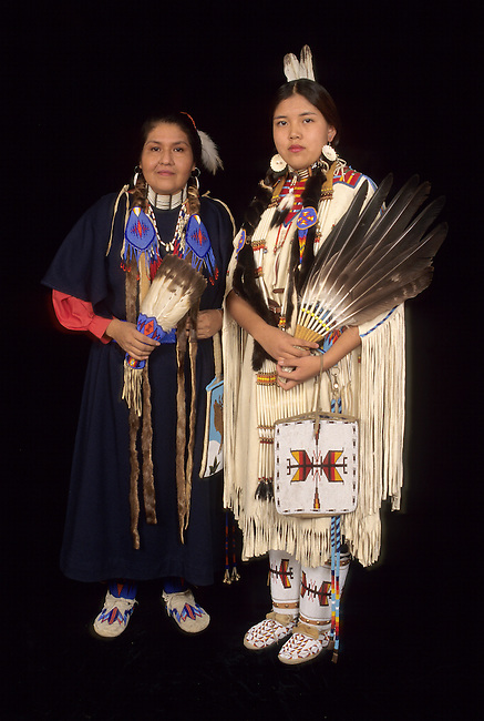 Native American family of mother in a trade cloth dress with teenage daughter who is dressed in traditional regalia and beadwork. Both carry eagle wing fans and wear beaded moccasins and carry beadwork bags.