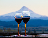 A pair of wine glasses in seen with red wine in the foreground with Mt Hood at sunset with an alpine glow in the background near Hood River, OR.