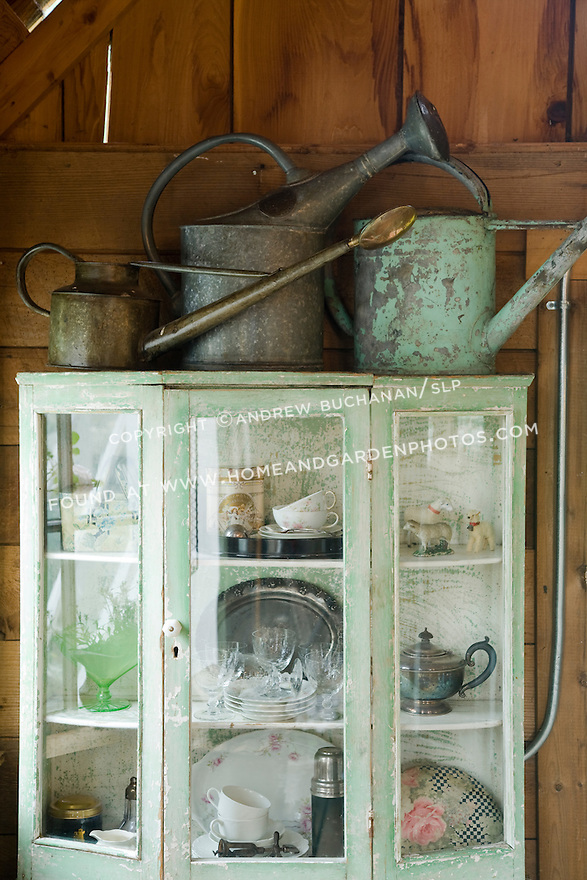 three worn watering cans sit atop a display cabinet of collectibles in this still life photo in a garden shed turned garden retreat.<br /> <br /> a 2-acre residential garden garden on rural property north of Seattle features recycled, reused, and repurposed materials, a romantic farmhouse cottage garden, and a white garden modeled on the famous garden at Sissinghurst.