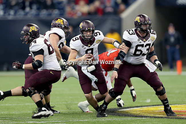 Minnesota Golden Gophers offensive linesman Jon Christenson (63), Minnesota Golden Gophers offensive linesman Caleb Bak (64) protect Minnesota Golden Gophers quarterback Philip Nelson (9) during the Meineke Car Care Bowl game of Texas between the Texas Tech Red Raiders and the Minnesota Golden Gophers at the Reliant Stadium in Houston, Texas. Texas leads Minnesota 24 to 17 at halftime.