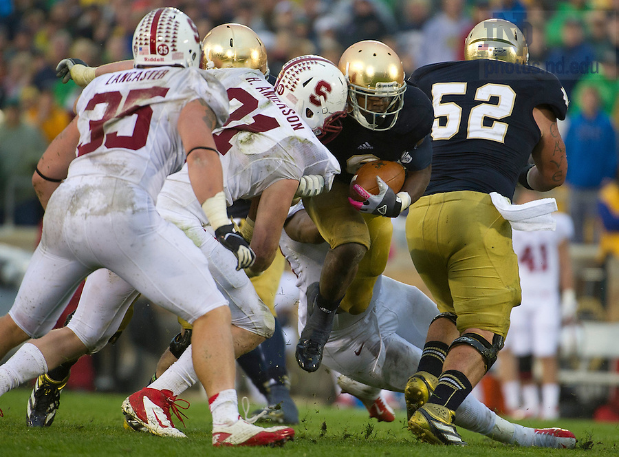 Oct. 13, 2012; Notre Dame running back Theo Riddick is stopped by defensive end Henry Anderson and linebacker Jarek Lancaster in the third quarter. Photo by Barbara Johnston/University of Notre Dame
