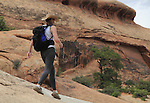 Woman walking on slickrock sandstone in Arches National PArk, Utah, USA. .  John offers private photo tours in Arches National Park and throughout Utah and Colorado. Year-round.