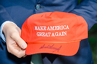 A person holds a Make America Great Again hat signed by President Donald Trump given by John Pence, nephew of Vice President Mike Pence and a 2020 Trump campaign senior advisor, as John Pence spoke with campaign volunteers and supporters outside the office of the New Hampshire Republican State Committee in Concord, New Hampshire, on Wed., Sept. 16, 2020. John Pence spoke to the crowd about the importance of their get out the vote efforts in securing a reelection victory for Donald Trump and Mike Pence.