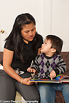 Two year old toddler boy with mother read to pointing at picture and talking