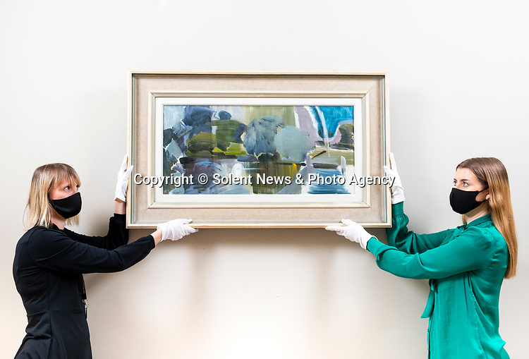 Pictured: Head of Modern & Contemporary Art Jennie Fisher and Sale Co-ordinator, Lulu Randall hang 'Wittenham Clumps from Days Lock', an oil on canvas piece by English artist Ivor Hitchens, with a value of £30,000 - £50,000 ahead of auction for the very first time at Dreweatts in Newbury, Berks.<br /> <br /> The piece, which has never been on the market before, will be available to the public as part of the Modern & Contemporary Art auction on March 18th 2021. <br /> <br /> Wittenham Clumps from Days Lock' is a landscape abstract panoramic piece by Hitchens and showcases the use of colour to create form. The typical sage green interspersed with greys, whites and violets draw the viewer over the water to the landscape beyond, with the intersecting lines of the foreground contrasting with the curve of the hills in the distance creating a sense of balance and harmony.  <br /> <br /> It was purchased as a wedding present by the parents of the current owners in 1957, directly from Hitchens at his studio and has remained with the same family ever since. <br /> <br /> © Jordan Pettitt/Solent News & Photo Agency<br /> UK +44 (0) 2380 458800