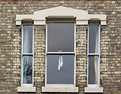 Bedfordshire, England. Ballet point shoes hanging in a window.