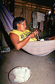 Koatinemo village, Brazil. Assurini woman lying in a hammock with cotton in a basket with spinning spindle and ball of thread.