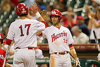 Taylor White #25 of the Houston Cougars high fives teammate Chase Jensen #17 after he scored a run against the Tennessee Volunteers at Minute Maid Park on March 2, 2012 in Houston, Texas.  The Cougars defeated the Volunteers 7-4.  (Brian Westerholt/Four Seam Images)
