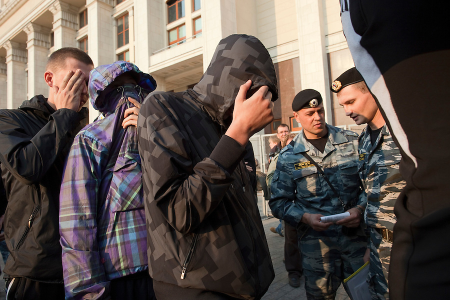 Moscow, Russia, 08/10/2011..Arrested youths hide their faces in Manezhnaya Square by the Kremlin as police detain some 100 young men to prevent a rumoured demonstration in memory of soccer fan Andrei Uryupin, who died in a fight on October 2nd. A similar gathering in the square for the death of another fan in December last year attracted 5,000 people who chanted nationalist slogans, and dark-skinned passers-by were attacked.