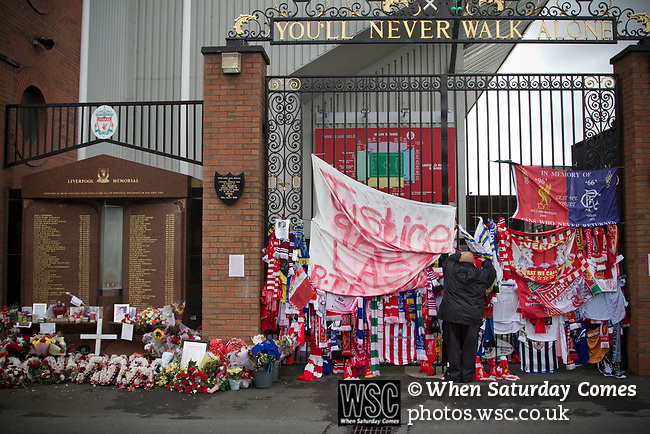A man attaching a scarf to the Shankly Gates next to the memorial at Anfield to the 1989 Hillsborough stadium disaster where 96 Liverpool football fans lost their lives. Mourners and well-wishers have been leaving flowers, scarves and wreaths after the publication of a report the previous week by the Hillsborough Independent Panel which released new information about the tragedy. The Hillsborough Justice Campaign had been campaigning for a new inquest into the disaster for the last 23 years. Photo by Colin McPherson.